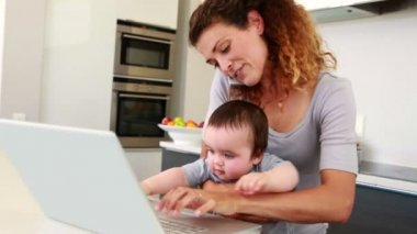 Mother sitting with baby boy on lap using laptop and talking on phone — Vidéo