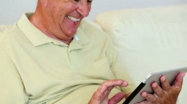 Senior man sitting on sofa using tablet — Stock Video