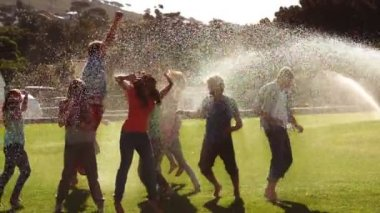 Students messing around in the sprinklers on the grass — Stock Video