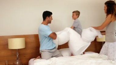 Parents and son having a pillow fight — Стоковое видео