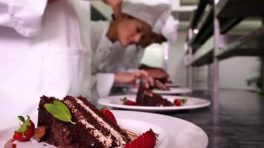 Chefs garnishing dessert plates with mint leaves and strawberries — Stock Video