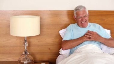 Senior man sitting in bed having a heart attack — Stock Video