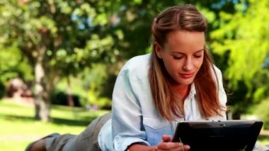 Blonde using her tablet lying on a blanket in the park — Stock Video