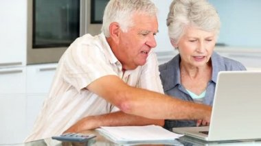 Senior couple using laptop to pay their bills — Stock Video