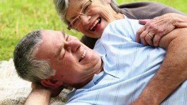 Affectionate senior couple relaxing in the park lying on blanket — Stock Video