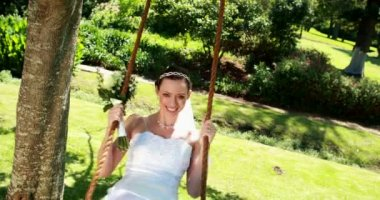 Smiling bride sitting on a swing — Stock video