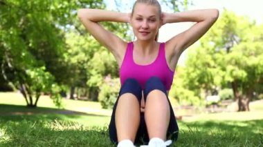 Fit blonde doing sit ups on the grass — 图库视频影像