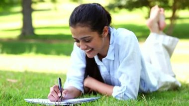Pretty girl lying on the grass writing on notepad — Stock Video