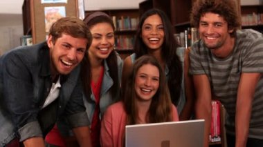 Happy students standing in the library with laptop — Vídeo de stock