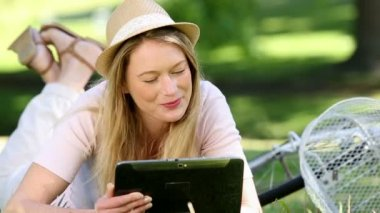 Pretty girl using tablet pc beside her bike in the park — Stock Video