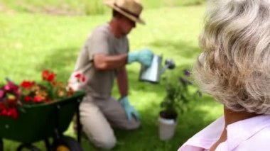 Retired woman watching her husband gardening — Stock Video