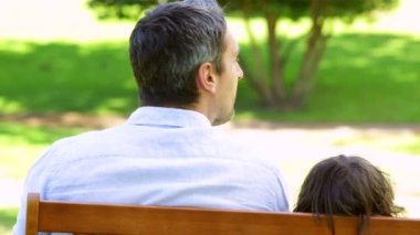 Father and son sitting on a park bench — Vídeo de stock