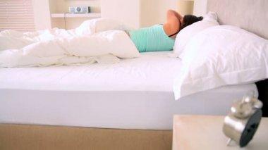 Sleepy brunette lying in bed — Stock Video