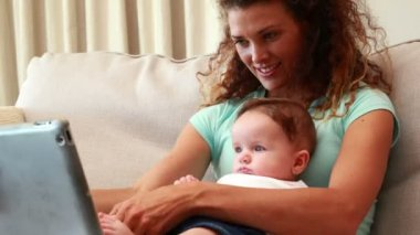 Mother using tablet pc with baby son on her lap — Stok video