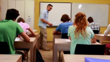 Lecturer handing out assignments to his students in classroom — Stock Video