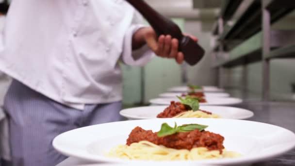 Chef condimento cenas de espaguetis con pimienta negra — Vídeo de stock
