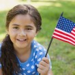 Young girl holding the American flag at park — Stock Photo #42915099