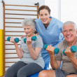 Therapist assisting senior couple with dumbbells — Stock Photo #42917199