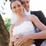 Bride and groom standing in garden — Stock Photo