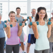 Class exercising with dumbbells in gym — Stock Photo #42918327
