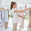 Saleswoman assisting woman with clothes — Stockfoto #42918339