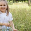 Young girl sitting in field — Stock Photo #42918497