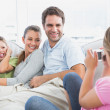 Little girl taking a photo of her family on the couch — Stock Photo #42918857