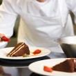 Mid section of pastry chef decorating dessert — Stock Photo