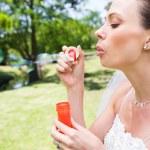 Bride blowing bubbles in garden — Stock Photo