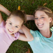 Happy mother and daughter lying on grass at park — Stock Photo #42919503