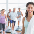 Cheerful woman with people exercising at fitness studio — Stock Photo #42919811
