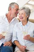 Senior couple sitting on couch drinking white wine — Stock Photo