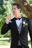 Bridegroom drinking champagne — Stock Photo