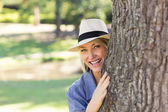 Woman hiding behind tree trunk — Stock Photo