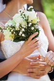 Mid section of a newlywed couple with bouquet in park — Stok fotoğraf