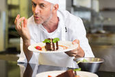 Smiling male pastry chef with dessert in kitchen — Stock Photo