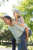 Couple enjoying piggyback ride in park — 图库照片