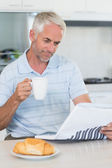 Happy man reading the newspaper at breakfast — Stock Photo