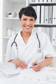 Portrait of a smiling doctor writing on clipboard — Stock Photo