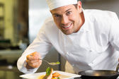 Smiling male chef garnishing food in kitchen — Stock Photo