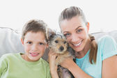 Smiling woman holding her yorkshire terrier puppy with her son — Stock Photo