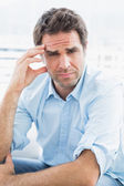 Wincing man with headache sitting on the couch looking at camera — Stock Photo