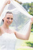 Bride unveiling self in garden — Stock Photo