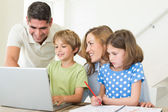 Family using laptop at table — Stock Photo