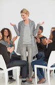 Rehab group applauding smiling woman standing up — Stok fotoğraf