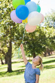 Young girl with colorful balloons at park — Foto Stock