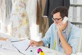 Stilista di moda maschile sorridente utilizzando il telefono in studio — Foto Stock