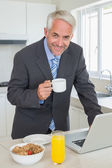 Happy businessman using laptop in the morning before work — Stock Photo