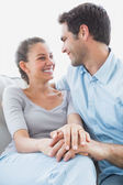 Excited couple looking at each other on the couch — Stock Photo