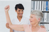 Physiotherapist assisting senior woman to stretch her hand — Stock Photo